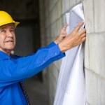 Senior man holding blueprints and wearing hardhat — Stock Photo