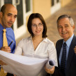 Three businesspeople holding a set of blueprints — Stock Photo