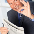 Businessmwith newspaper giving okay sign — Stock Photo #36340741