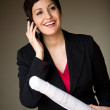 Businesswoman on cellphone holding blueprints — Stock Photo