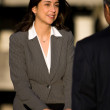 Business woman looking at approaching businessman — Stock Photo