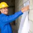 Senior man holding blueprints — Stock Photo