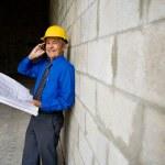 Senior man holding blueprints — Stock Photo