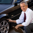 Car Salesman Checking Car's Tire — Stockfoto