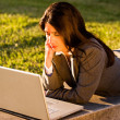 Businesswoman lying on a bench with Laptop — Stock Photo