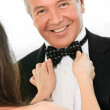 Female fixing mature man's bow tie — Stock Photo