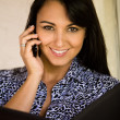 Stock Photo: Businesswomholding portfolio and talking on cellphone