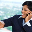 Businesswoman on cellphone looking at watch — Stock Photo