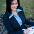 Stock Photo: Smiling businesswomsitting outdoors