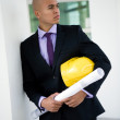 Man holding hard hat and blueprints — Stock Photo