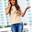 Stock Photo: Smiling female walking and talking on cellphone