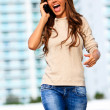 Female laughing while on cellphone — Stok fotoğraf