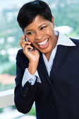 African descent smiling businesswoman on mobile phone — Stock Photo