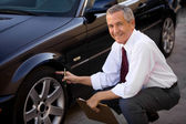 Car Salesman Checking Car's Tire — Stock Photo