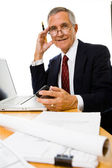 Senior businessman sitting at desk — Stock Photo