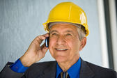 Senior man wearing hardhat and holding cellphone — Stock Photo