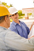 Two construction workers examining a set of blueprint — Stock Photo
