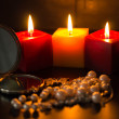 Burning candles, pocket mirror and beads — Stock Photo