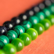 Green and black beads from a stone on a coral background — Stock Photo #31337841