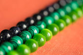 Green and black beads from a stone on a coral background — Stock Photo