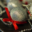 Chain and a silvery ball with a red bow — Stock Photo #35537659