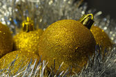 Gold Christmas spheres on a silvery background — Stock Photo
