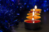 A row from burning candles and a Christmas decor — Stock Photo