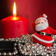 Red candle with a decor from silver balls and toy Santa Claus — Stock Photo