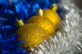 Gold Christmas spheres among a silver and blue decor close up — Stock Photo