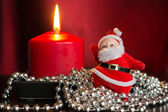 Red candle with a decor from silver balls and toy Santa Claus — Stok fotoğraf