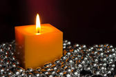 Yellow candle with a decor from silver balls — Stock Photo