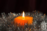 Yellow candle with a silvery Christmas decor — Stock Photo