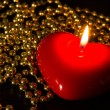 Stock Photo: Red candle in form of heart with gold beads