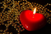 Red candle in the form of heart with a gold beads — Stock Photo