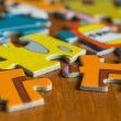 Stock Photo: Children's puzzle scattered on wooden table close up