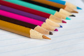 The color pencils lying on an open writing-book — Stock Photo