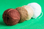 A row from balls of a multi-colored yarn on a green background — Stock Photo