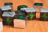 Group of chocolates in a paper wrapper with a bow — Stock Photo