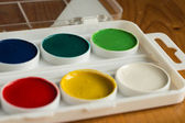 Box with water color paints of different color on a wooden surface — Stock Photo