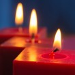 A row from three burning red candles — Stock Photo #42792531