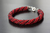 Knitted bracelet from beads of two shades of red color — Stock Photo