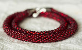 Necklace from red beads on a textile background — Stock Photo