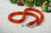 Orange necklace from beads among dry petals — 图库照片