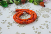 Halskette aus hellen orange perlen auf einem textil-hintergrund — Stockfoto