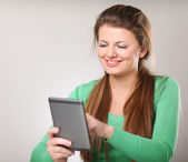 Young woman sitting on the desk holding computer tablet — Stock Photo