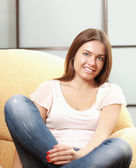 A young smiling woman sitting on the sofa — Stok fotoğraf