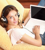 A woman working on a laptop sitting on sofa — Stock Photo