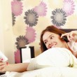 teenager girl lying on a bed reading a book and talking on a mobile phone  — Stock Photo