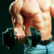 Muscular man working out with dumbbells — Stockfoto