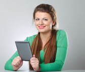 Woman sitting on the desk and holding computer plane-table — Stock Photo